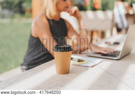 Coffe Cup. Coffee To Go. Adult Woman Typing At Laptop And Mobile Cell Phone Outside In Park. Thinkin