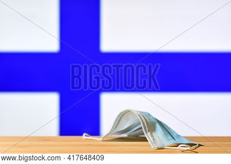 A Medical Mask Lies On The Table Against The Background Of The Flag Of Finland. The Concept Of A Man