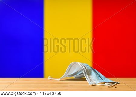 A Medical Mask Lies On The Table Against The Background Of The Flag Of Romania. The Concept Of A Man