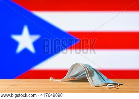 A Medical Mask Lies On The Table Against The Background Of The Flag Of Puerto Rico. The Concept Of A
