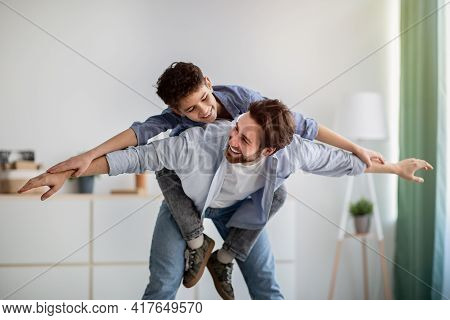 Excited Boy Playing With Happy Father At Home, Dad Piggybacking Son, Carrying On Back Like Flying On