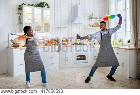 Full Length Of Black Man And Woman Fighting With Mop, Spray And Duster At Kitchen, Having Fun During