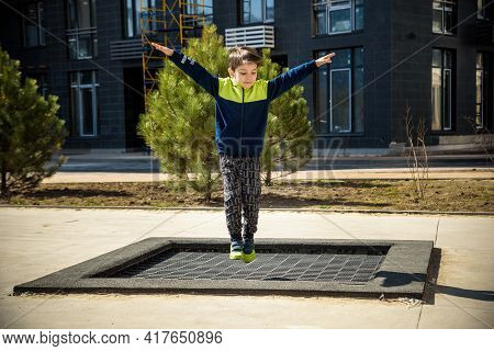 Little Boy Playing On The Field At The Day Time. People Having Fun Outdoors. He Jumping On Trampolin