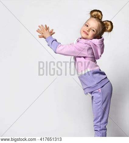 Studio Shot Of Little Blond Girl Wearing Pink Violet Sportive Suit With Hood Posing For Camera With
