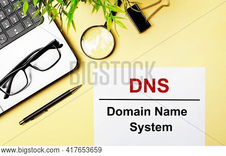 Dns Domain Name System Is Written In Red On A White Piece Of Paper On A Light Yellow Background Next