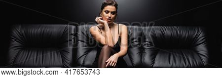 Sexy Woman In Slip Dress And Tights Sitting On Sofa On Black Background, Banner.
