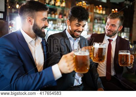 Meeting With The Best Friends. Happy Young Business Men Talking And Drinking Beer In A Pub
