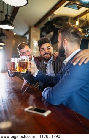 Group Of Happy Friends Drinking Beer At The Pub And Having Fun