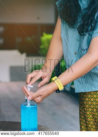 Hands Of Senior Woman Pressed Blue Alcohol Gel Bottle To Prevent The Spreading Of The Coronavirus (c