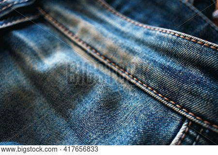 Blue Denim Jeans With Yellow Stitching. Close-up Of A Fashionable Fabric. Textile Background