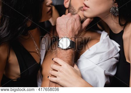 Partial View Of Passionate Women Seducing Young Man On Blurred Background.