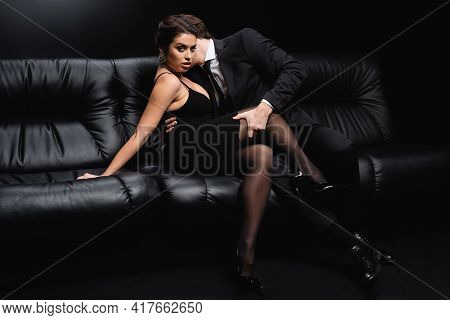 Man In Suit Seducing Sexy Woman In Slip Dress Sitting On Sofa On Black.