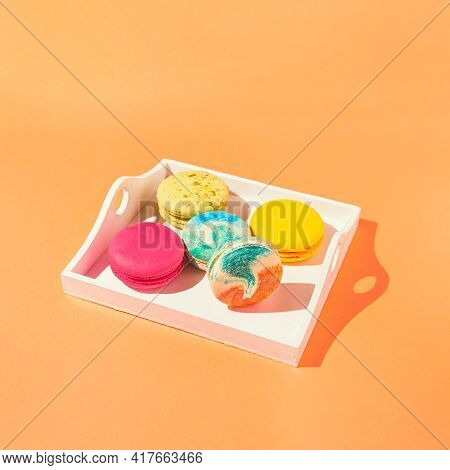 Assortment Of Colorful Macaroons On White Wooden Tray On Orange Background With Sunlit. Dessert Conc