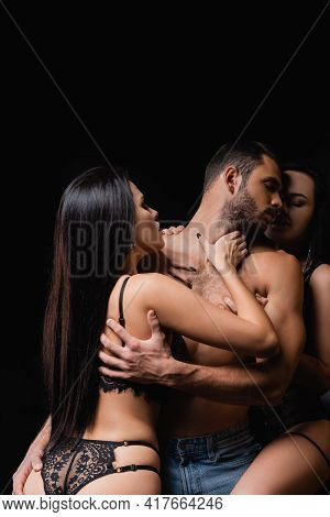 Sexy Women In Lace Lingerie Seducing Shirtless Man Isolated On Black.