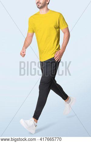 Man in yellow t-shirt and black pants sportswear fashion