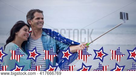 Composition of american flag stars over happy couple taking selfie with smartphone on selfie stick. american patriotism, culture and tradition concept digitally generated image.
