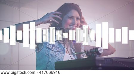 Composition on graphic music equalizer over smiling female dj putting headphones on in club. entertainment, music and clubbing concept digitally generated image.