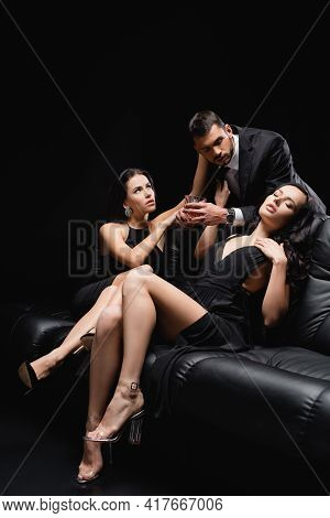 Man In Suit Holding Glass Of Whiskey Near Seductive Women On Leather Couch Isolated On Black.