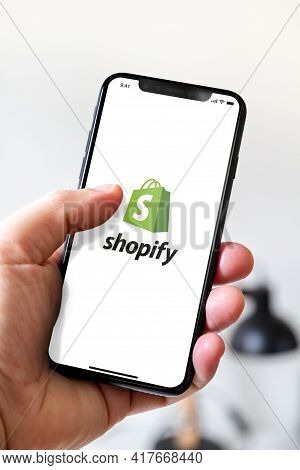 Paris - France - March 23, 2021 : Hand Holding Iphone Smartphone With Shopify Logo