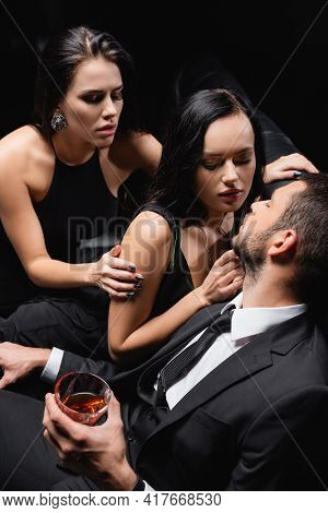 Man Holding Glass Of Whiskey Near Sexy Women Seducing Him Isolated On Black.