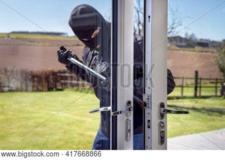Burglar or thief breaking into a home through window with a crowbar