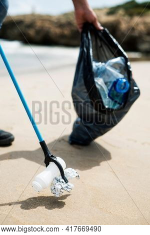 a man collects with a reach extender some waste, such as cans, bottles or bags, from the sand of a lonely beach, as an action to clean up the natural environment