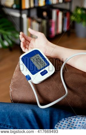 closeup of a caucasian man, sitting comfortably in a sofa, measuring his own blood pressure with an electronic sphygmomanometer