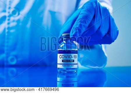 a healthcare worker man, wearing blue surgical gloves, shows a simulated covid-19 vaccine bottle on a blue table