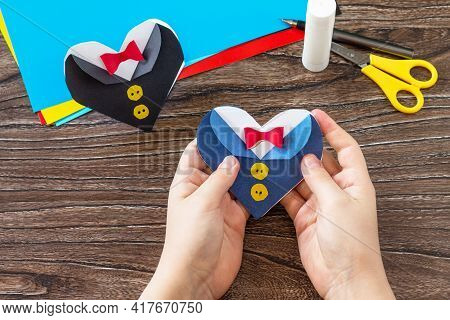 The Child Holds In His Hands A Greeting Card For On Father's Day Heart With Tuxedo On Wooden Table.