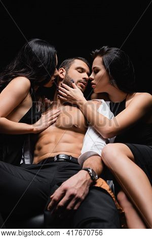 Sexy Man In Unbuttoned Shirt Sitting On Leather Couch Near Passionate Women Isolated On Black.