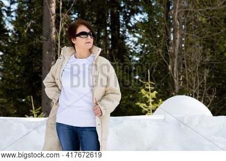 White Fleece Crewneck Sweatshirt Mockup Featuring A Woman Wearing Beige Quilted Coat In The Snowy Wo