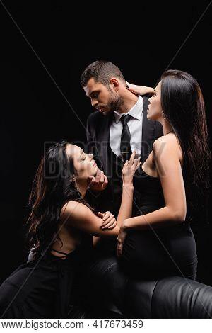 Passionate, Elegant Women Seducing Man In Suit Isolated On Black.