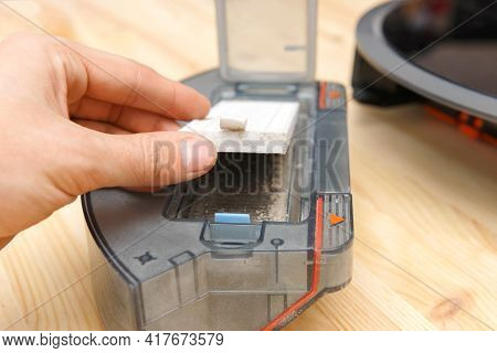 Human Takes Out A Dust Container In A Robotic Vacuum Cleaner.