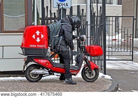 Kiev, Ukraine - Feb 02, 2021: Unknown Young Nova Poshta Courier In Black Suit On Motorcycle Delivers