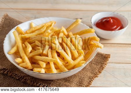 Hot Golden French Fries With Ketchup On Wooden Background. Tasty American Fast Food.
