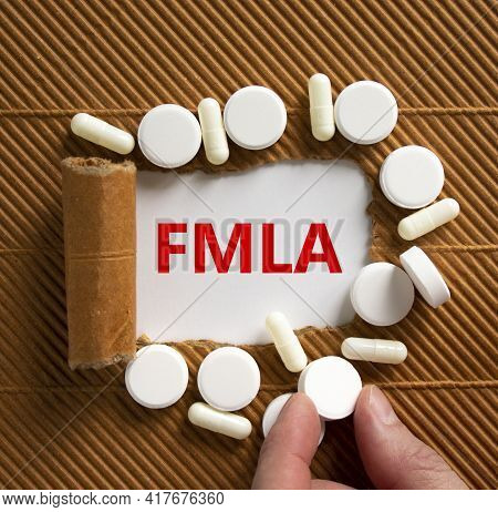 Fmla, Family Medical Leave Act Symbol. Words 'fmla, Family Medical Leave Act' Appearing Behind Torn