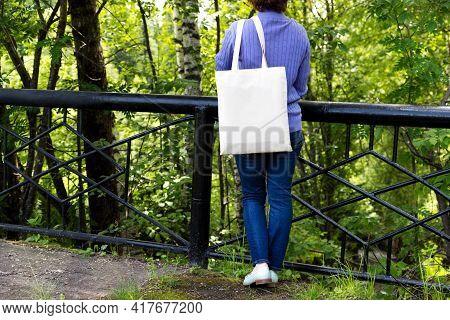 Woman Standing Near Bridge Railing, Empty Reusable Shopping Bag Mockup. Female Hand Holding Canvas E