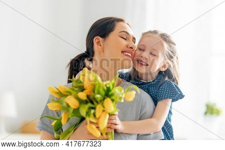 Happy mother's day. Child daughter congratulates mom and gives her flowers. Mum and girl smiling and hugging. Family holiday and togetherness.