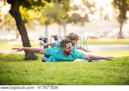 Father Lying On Grass, With Excited Happy Little Child Son On Shoulder. Weekend Man Family Concept.