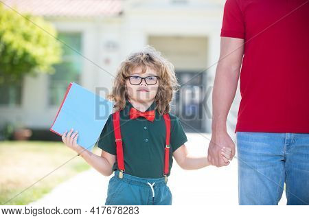 Portrait Of Happy Nerd Pupil Holding Teachers Hand. Father Holding Hand Of Son With Backpack Outdoor