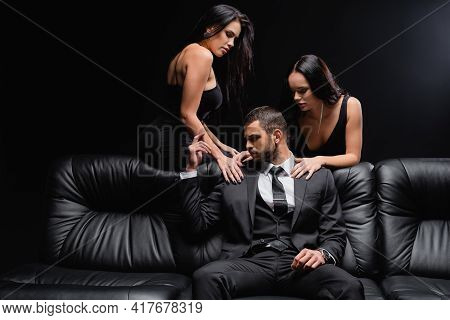Passionate Women Seducing Man In Suit Sitting On Leather Couch Isolated On Black.