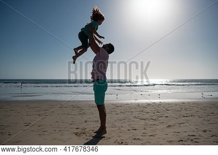 Father Throws Son Up Against The Blue Sky. Dad Throwing Child. Handsome Man Father Carrying Young Bo
