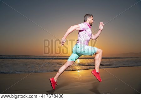 Man Runner Jogger Running. Young Guy Running Along The Beach Of The Sea During An Amazing Sunset.