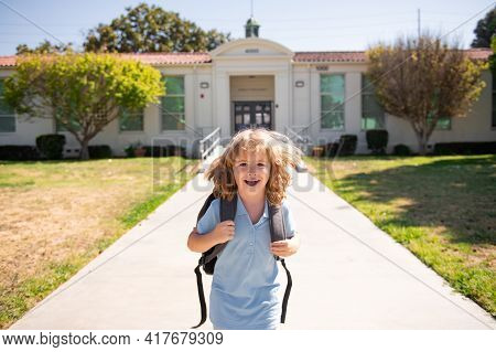 Portrait Of Schoolchild Running On Playground At End Of Class. Funny Happy School Boy Face. The Begi