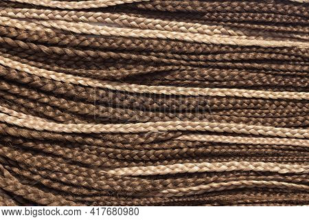 Texture Of Thin Brown African Braids, Hair Close-up Braided In Pigtails Dreadlocks, Afro Style.