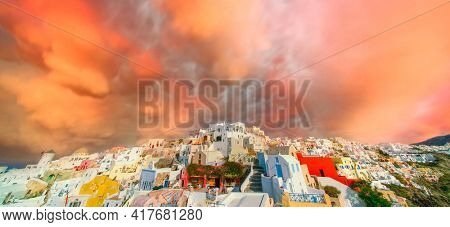 Oia village on Santorini island under orange sunset sky