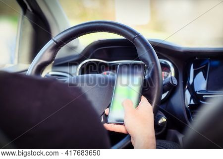 Young Man Driver Using Mobile Phone In Car, Hand Holding Smart Phone And Driving And Texting, Transp