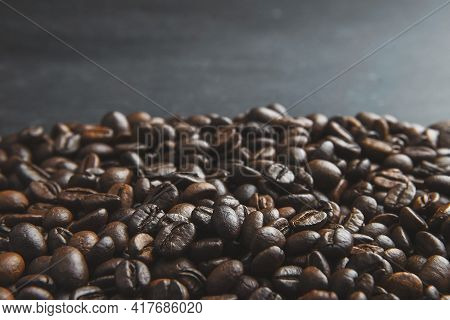 Roasted Coffee Beans On A Stone Background. Coffee Beans Texture. Coffee In Beans On Dark Background