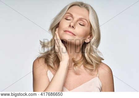 Gorgeous Senior Older Woman With Closed Eyes Touching Her Perfect Skin. Beautiful Portrait Mid 50s A