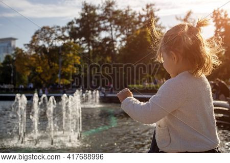 Adorable Little Girl Looks At The Fountain. Toddler In A Park With Fountains On A Sunny Day.. Family